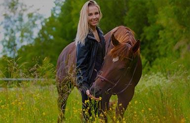 Kvinna och häst står på en äng